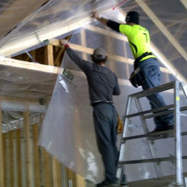 Men putting up plastic sheeting